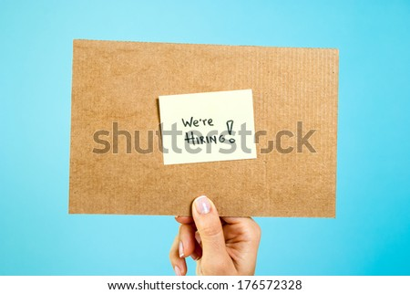 """Hand holding a cardboard with a sticky note """"We are hiring!"""" on vibrant blue background. Recruitment concept. - stock photo"""
