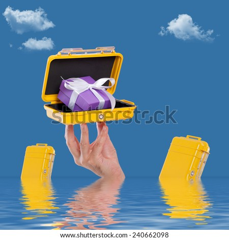 Hand holding a case with a gift in the water - stock photo