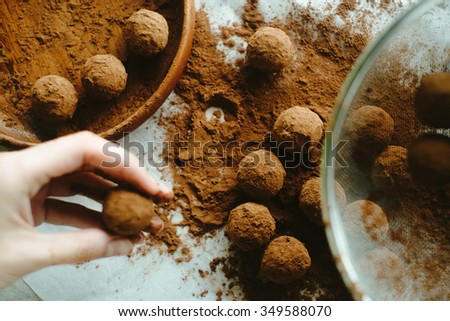 Hand holding a chocolate truffle - stock photo
