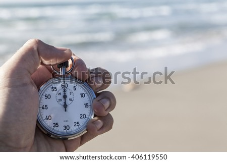 Hand holding a chronometer and sea in the background - stock photo