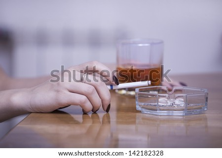 hand holding a cigarette and a glass of whiskey