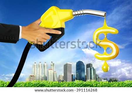 hand holding a classic fuel nozzle giving a oil drop as dollar sign with city background