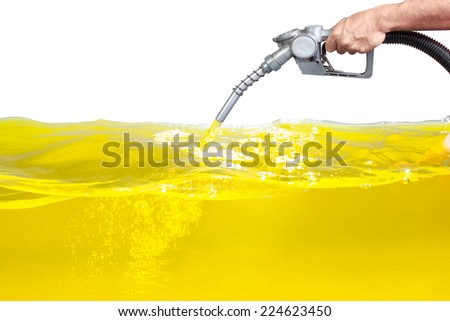 Hand holding a classic fuel nozzle pumping a gasoline fuel liquid in a tank of oil Industry isolated on white background with clipping path - stock photo