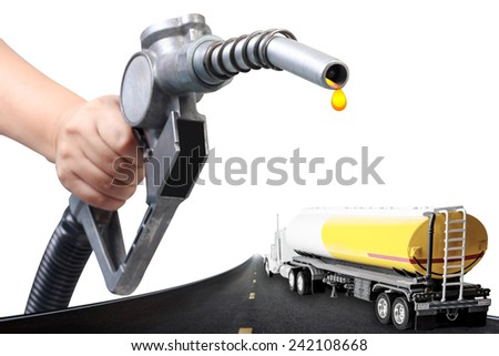 Hand holding a classic fuel nozzle pumping and truck with fuel tank on the highway  - stock photo
