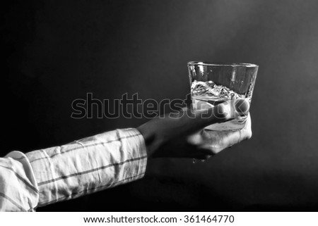 Hand holding a clear glass of water on a black background close up