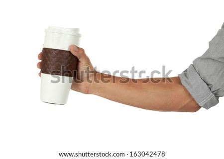 Hand holding a coffee mug out to the side - stock photo