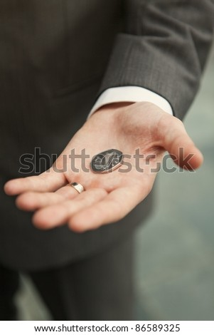 Hand holding a coin in his palm. - stock photo