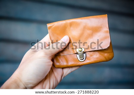 Hand holding a coin purse,  color vintage purse - stock photo