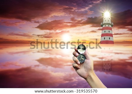 Hand holding a compass on sunset and lighthouse background. - stock photo