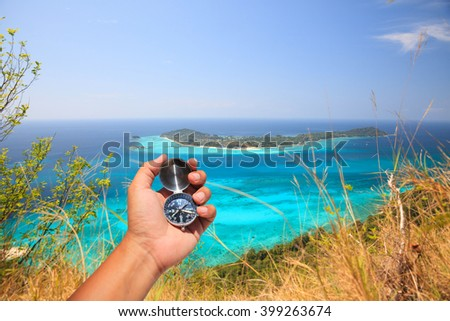 Hand holding a compass on the island background. - stock photo