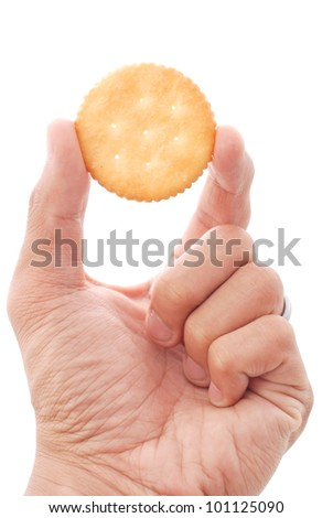 hand holding a cracker against white background