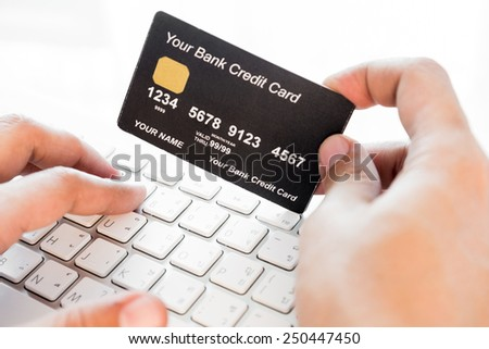 hand holding a credit card and typing. On-line shopping on the internet - stock photo