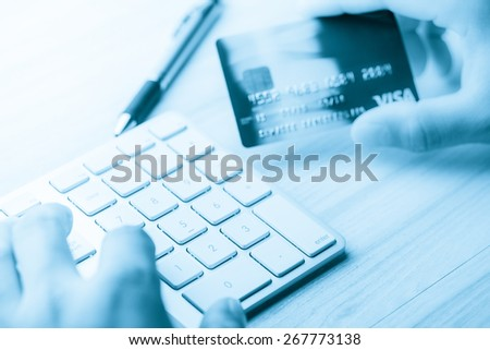 hand holding a credit card and typing. On-line shopping on the internet in blue tone - stock photo