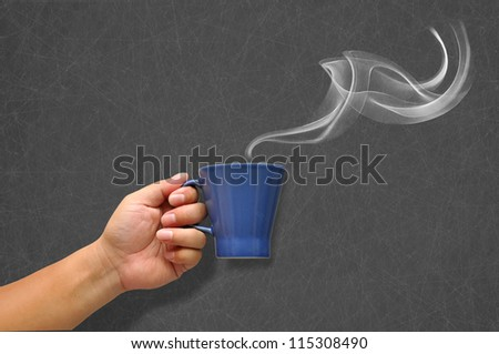 Hand holding a cup of coffee with white smoke - stock photo