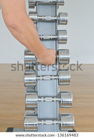 Hand holding a dumbbell in row on stand