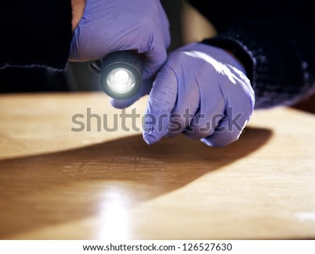 Hand holding a flashlight and searching for evidence - stock photo