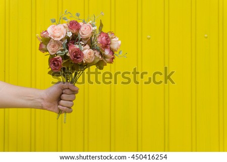 Hand holding a flower with yellow background