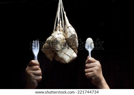 hand holding a fork and spoon to eat ketupat isolated  black background.Ketupat is traditional food in Malaysia for celebration - stock photo