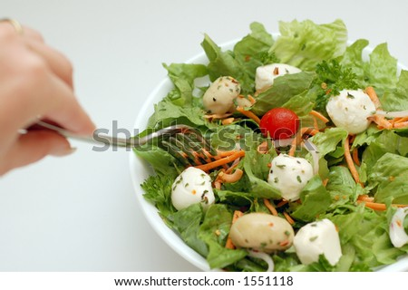 Hand holding a fork over salad