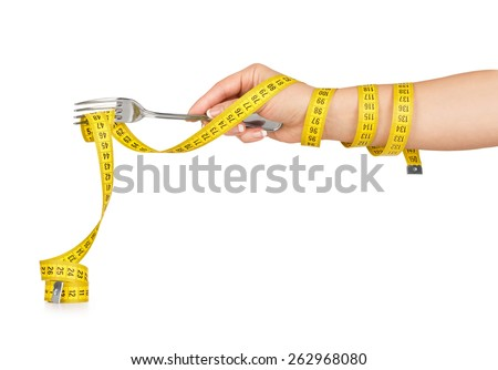 hand holding a fork with a measuring tape on a white background - stock photo