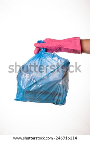 Hand holding a full blue plastic trash bag - stock photo