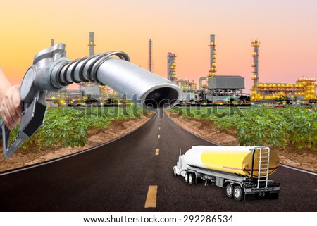 Hand holding a gasoline fuel nozzle and tanker truck into of highway to petrochemical oil refinery in sunrise - stock photo