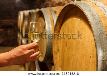 Hand holding a glass of cold white wine in front of oak barrels - stock photo