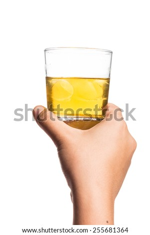 Hand holding a glass of diluted whiskey on the rock - stock photo