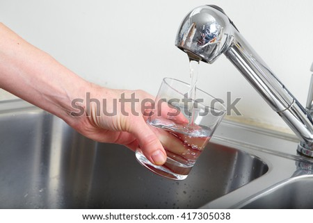 Hand holding a glass of water poured from the kitchen faucet. - stock photo