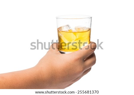 Hand holding a glass of whiskey on the rock - stock photo
