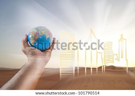 Hand holding a Globe. Buildings of Development on a Desert Landscape - stock photo