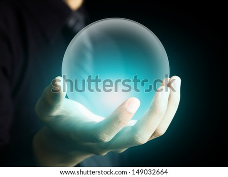 Hand holding a glowing crystal ball - stock photo