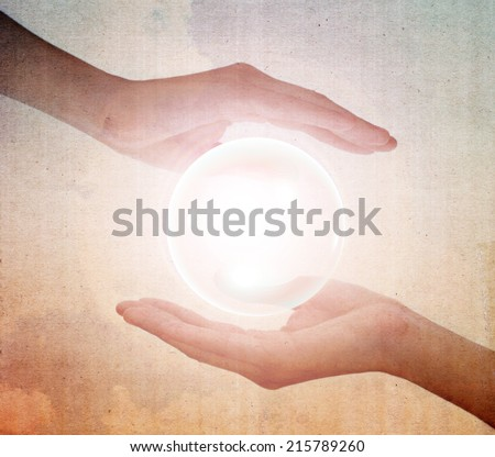 Hand holding a glowing crystal ball on vintage background. Filtered image. - stock photo