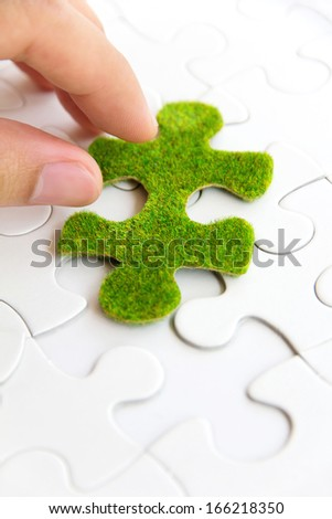 hand holding a green puzzle piece, green space concept  - stock photo