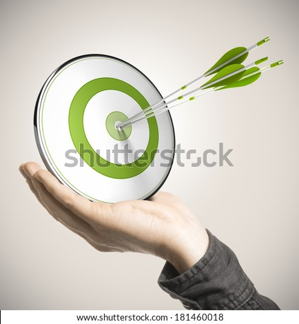 Hand holding a green target with three arrows hitting the center over beige background. Business performance concept. - stock photo