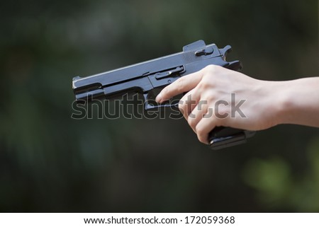 Hand holding a gun - stock photo