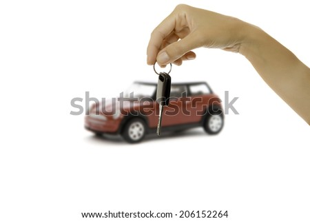 hand holding a key and a red miniature car at background isolated on a white background - focus on hand and key - stock photo