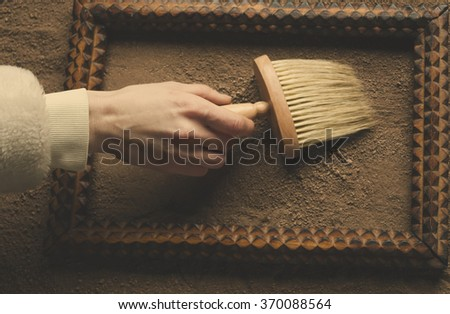 hand holding a large brush on the background of a wooden frame and sand