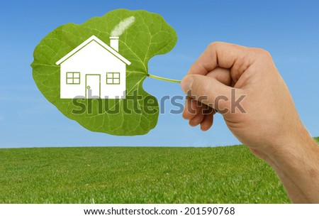 Hand holding a leaf with a house symbol on a new development site - stock photo