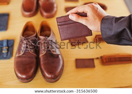 hand holding a leather wallet over other accessories set