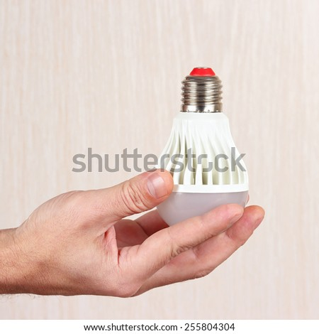 Hand holding a light bulb on a light wood background - stock photo