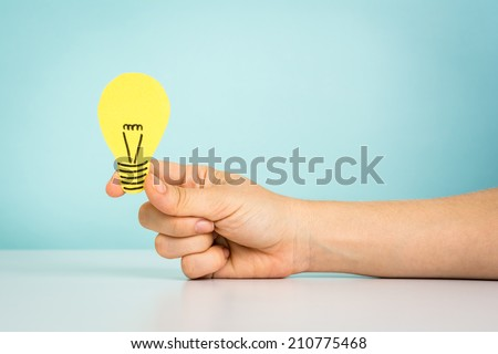 Hand holding a light bulb on blue background - stock photo
