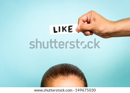 """Hand holding a """"like"""" message over top of woman head, on blue background. Thinking concept. - stock photo"""