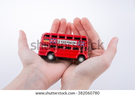 Hand holding a London double decker bus on a white background - stock photo