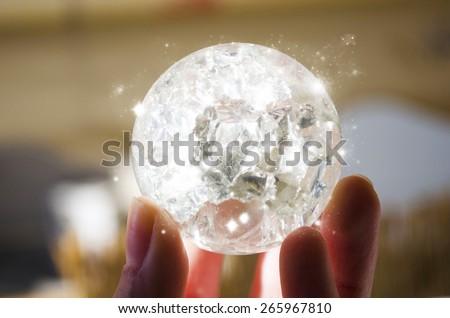 Hand holding a magic crystal ball - stock photo