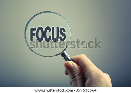 Hand holding a magnifying glass with text Focus. - stock photo