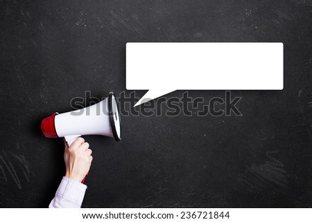 hand holding a megaphone with a speech bubble - stock photo