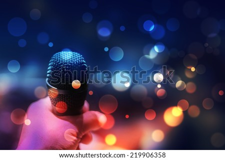 hand holding a microphone against colourful background - stock photo