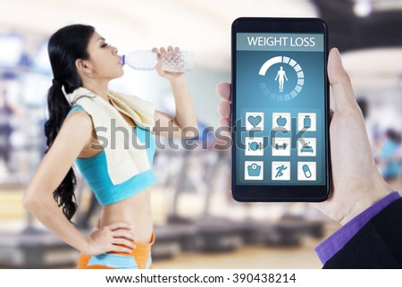 Hand holding a mobile phone with health monitoring application on the screen, shot with young woman drinking water at gym - stock photo