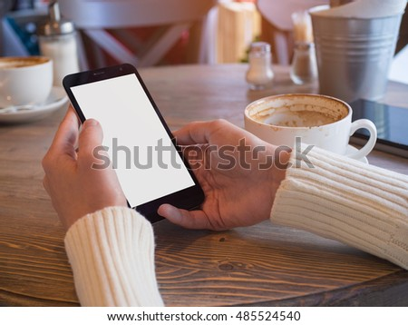 Hand holding a mobile phone with isolated screen for your information. Girl reads the news on the phone sitting in a cafe for a wooden table and finishing off a delicious coffee